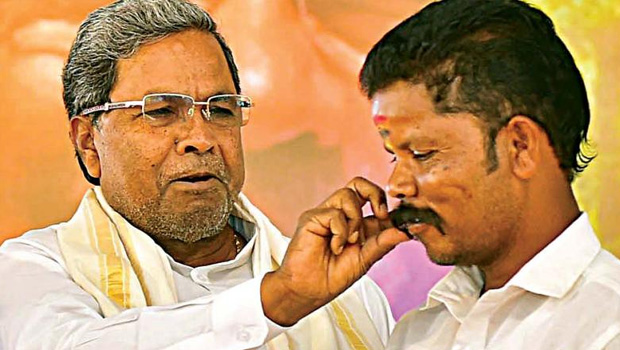 siddaramaiah giving to land papers to tribal peoples